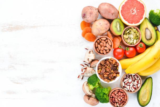 Alimentos contendo potássio natural. K: batatas, cogumelos, banana, tomates, nozes, feijão, brócolis, abacates. Vista superior. Em um fundo de madeira branco. - foto de acervo