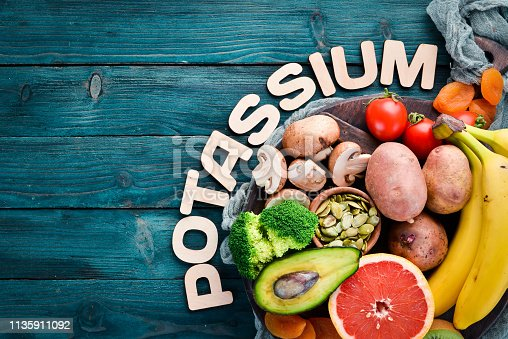 Foods containing natural potassium. K: Potatoes, mushrooms, banana, tomatoes, nuts, beans, broccoli, avocados. Top view. On a blue wooden background.