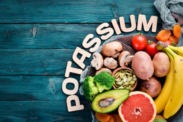 Alimentos contendo potássio natural. K: batatas, cogumelos, banana, tomates, nozes, feijão, brócolis, abacates. Vista superior. Em um fundo de madeira azul. - foto de acervo