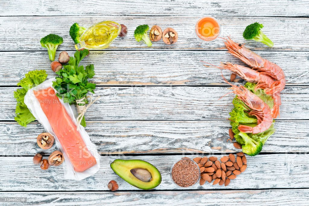 Foods containing omega 3. Vitamin Healthy foods: avocados, fish, shrimp, broccoli, flax, nuts, eggs, parsley. Top view. Free space for your text. On a white wooden background. stock photo