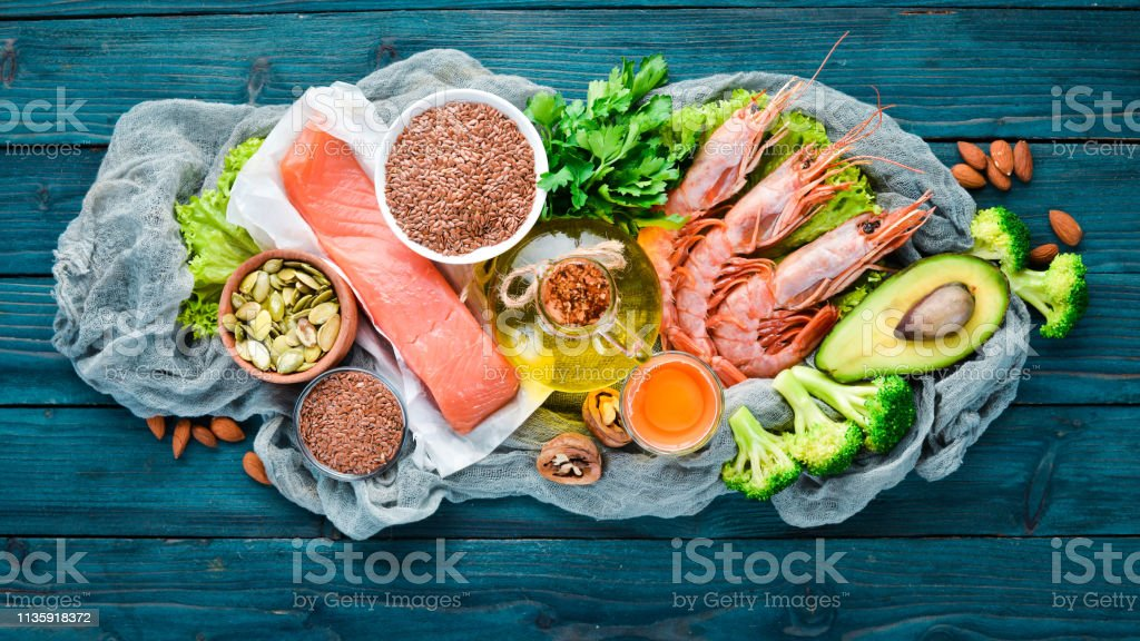 Foods containing omega 3. Vitamin Healthy foods: avocados, fish, shrimp, broccoli, flax, nuts, eggs, parsley. Top view. Free space for your text. On a blue wooden background. stock photo