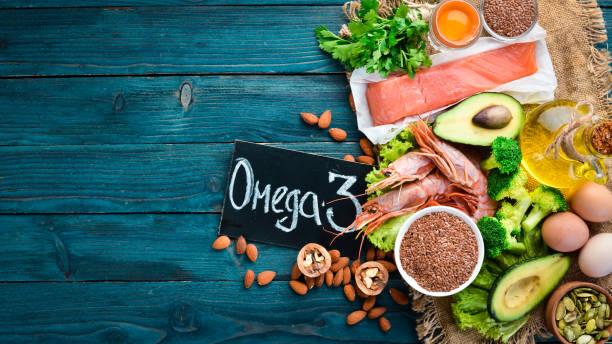 Alimentos contendo ômega 3. Alimentos saudáveis da vitamina: abacates, peixes, camarão, brócolis, linho, porcas, ovos, salsa. Vista superior. Espaço livre para o seu texto. Em um fundo de madeira azul. - foto de acervo