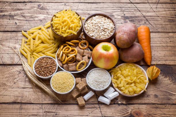 alimentos ricos en hidratos de carbono en el fondo de madera rústica. - carbohidrato fotografías e imágenes de stock