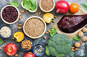 Foods high in iron. liver, broccoli, persimmon, apples, nuts, legumes spinach pomegranate Top view flat lay