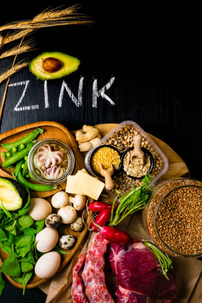 富含鋅的食品有章魚、牛肉、蕎麥、黃乾酪、菠菜、avokado、豌豆、蘑菇、豆類、蘿蔔、蛋等。頂部視圖 - 鋅 個照片及圖片檔