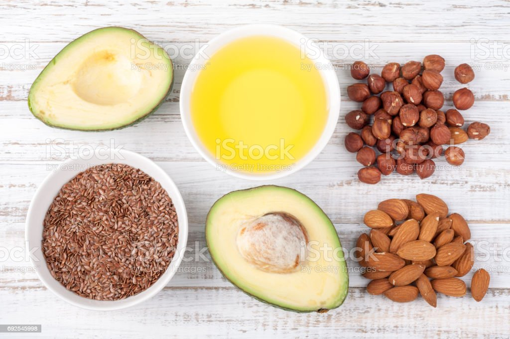 Foods with healthy fats. Sources of omega 3 - avocado, olive oil, nuts and flax seed on wooden background. Healthy food concept. Top view stock photo