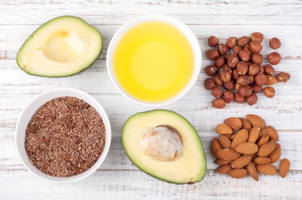 食品與健康的脂肪。來源的歐米茄 3-鱷梨、 橄欖油、 堅果和亞麻籽木背景上。健康食品的概念。頂視圖 - 脂肪 營養 個照片及圖片檔
