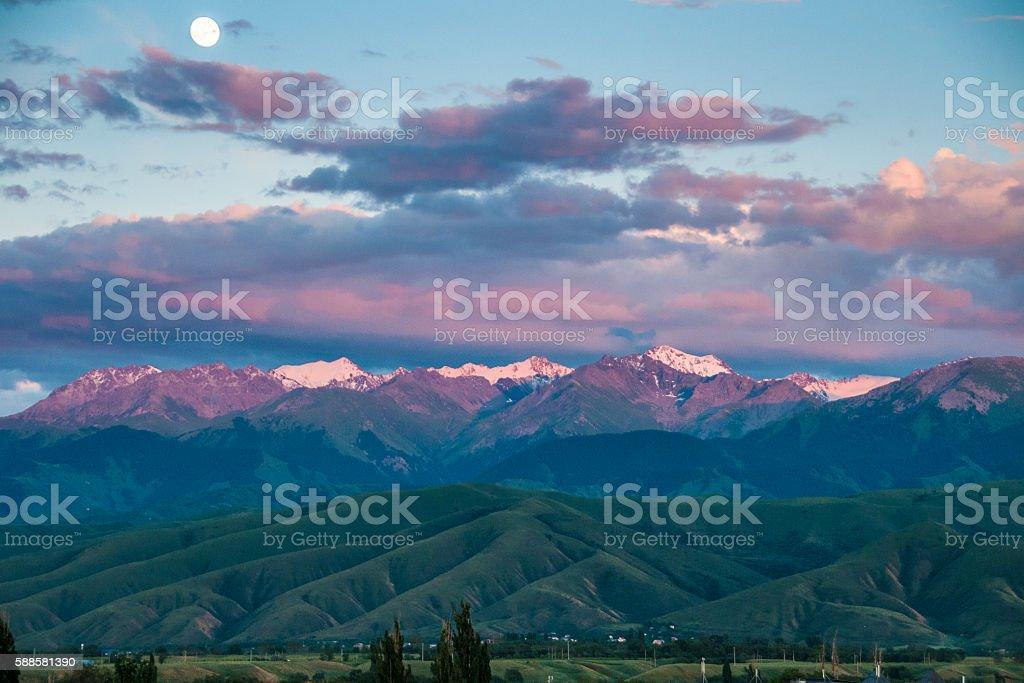 Fool moon ans sunset sky over mountains stock photo