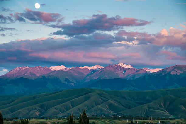 Fool moon ans sunset sky over mountains stock photo
