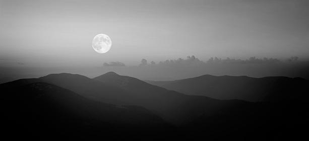 Fool moon rising over the mountain range in Carpathians