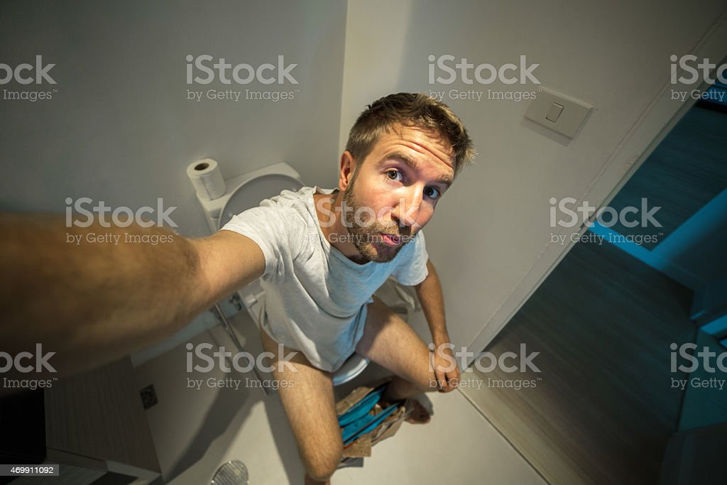 Fool young man taking selfie on toilet-Bathroom stock photo