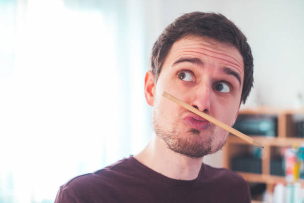 fooling around at home. bored young man with a trapped pencil between nose and lips - dawdle stock pictures, royalty-free photos & images