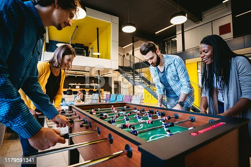 Young beautiful coworkers playing table football on break in office.