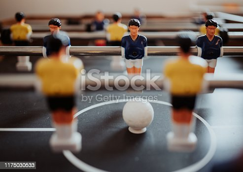 Detail shot of a foosball game with yellow and blue players.