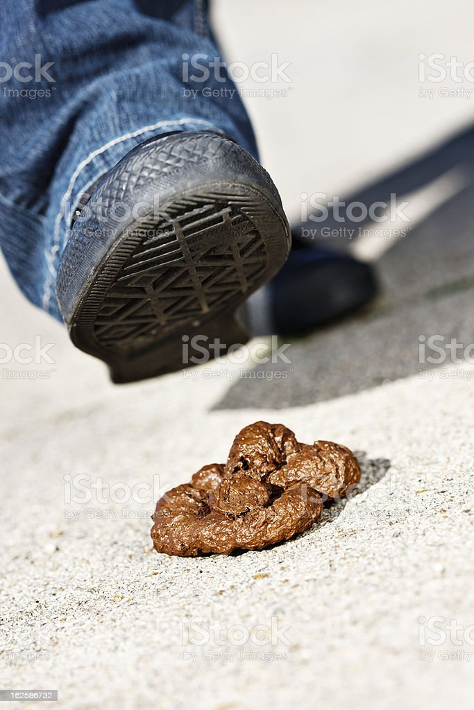 Foot aproaching dog droppings - urban accident on the way! stock photo