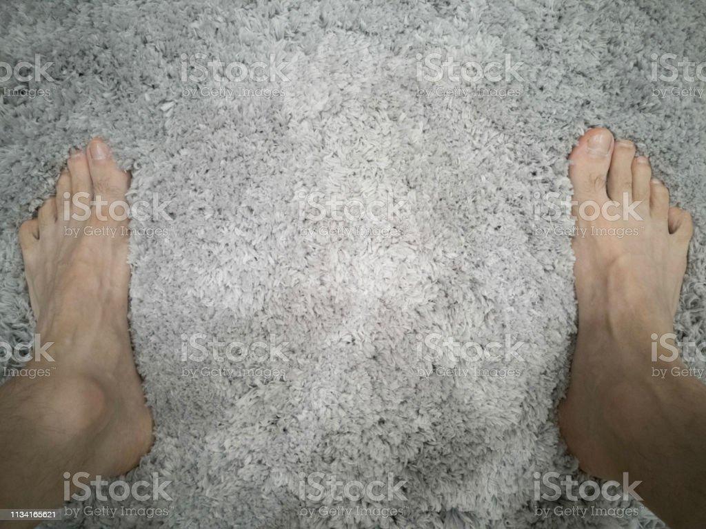 Foot at the bathroom floor stock photo