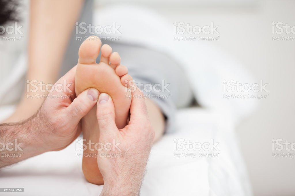 Foot being massaged on a medical table Foot being massaged on a medical table in a room Barefoot Stock Photo