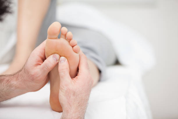 Foot being massaged on a medical table stock photo
