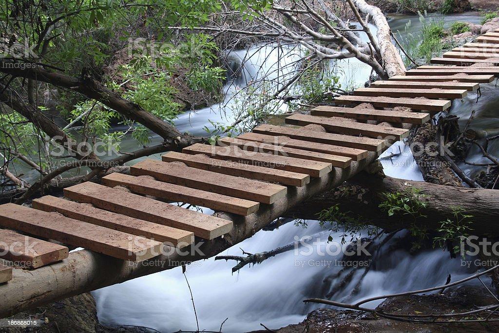 Foot Bridge Across Flowing Creek royalty-free stock photo