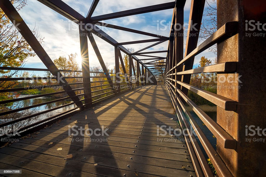 Foot bridge crosses a river on an autumn morning stock photo