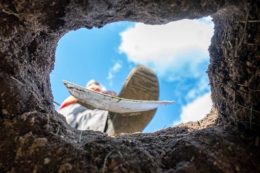A gardener digs a hole with a spade, photographed from below from the hole towards the sky.