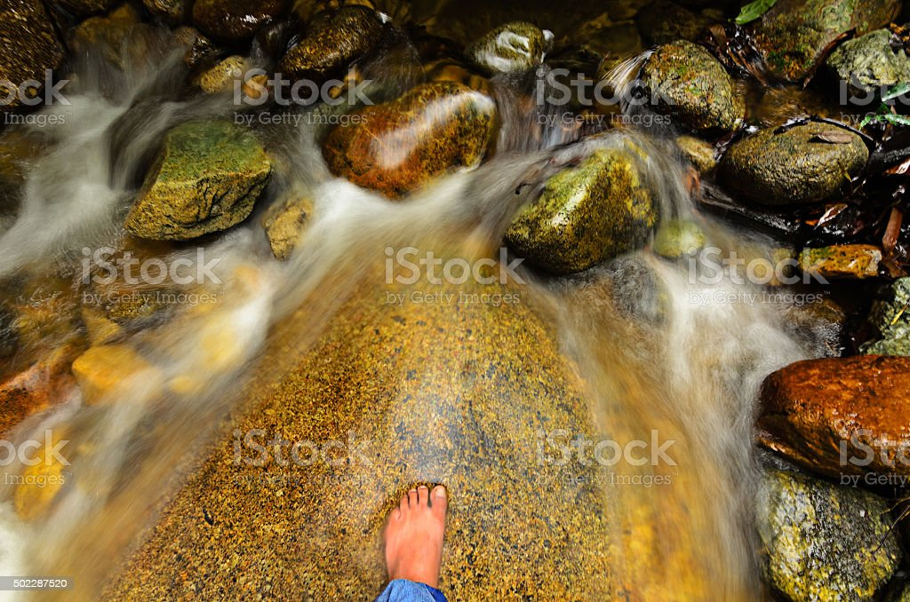 foot in cold water flow stock photo