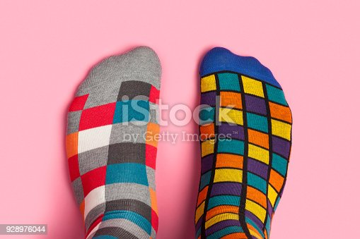 Foot in different colorful socks on pink background. This file is cleaned and retouched.
