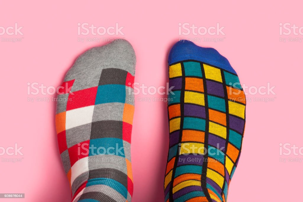 Foot in different colorful socks on pink background stock photo