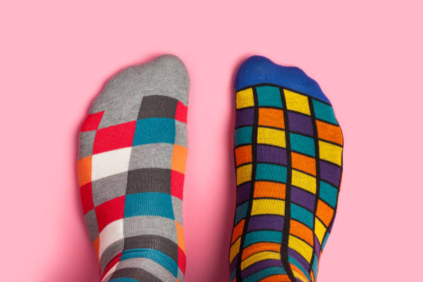 foot in different colorful socks on pink background - contrasti foto e immagini stock