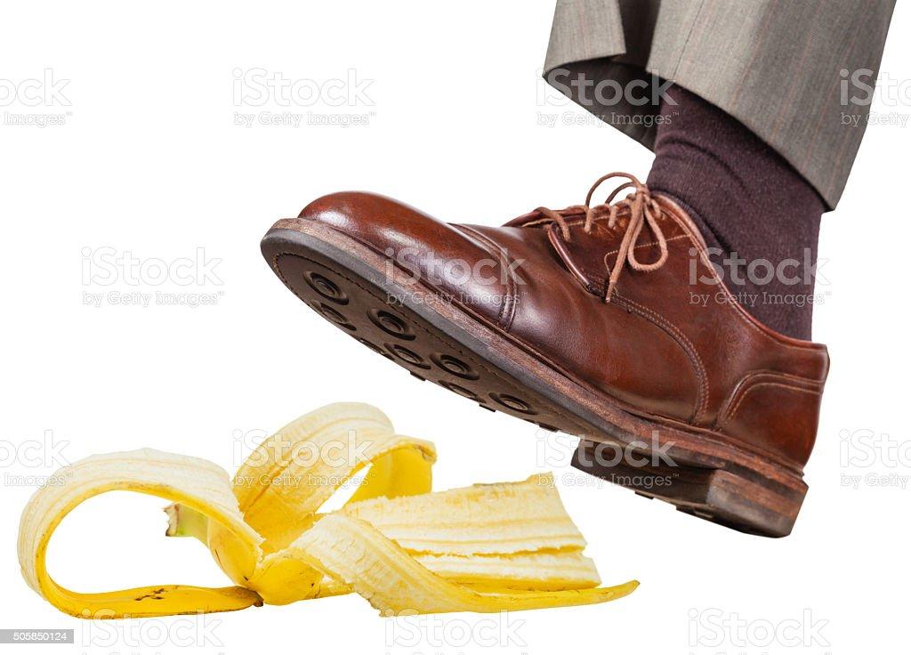 foot in the left brown shoe slips on banana peel stock photo