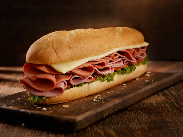 Foot Long Pizza Sub 12 inch - Salami, Pepperoni and Mozerella Cheese Submarine Sandwich with Lettuce and Tomato on a Crusty Bun- Photographed on Hasselblad H3D2-39mb Camera submarine sandwich stock pictures, royalty-free photos & images