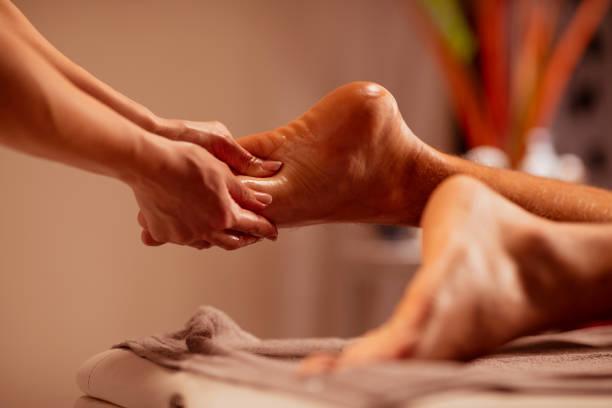 Foot massage. Massage Therapist woman doing healing massage. Man enjoying in relaxing massaging at health spa treatment. stock photo