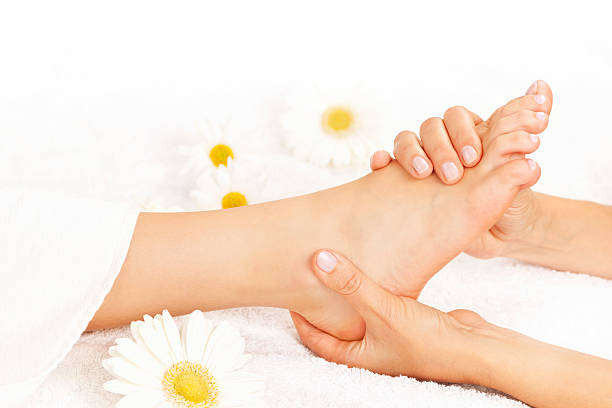Foot massage Female hands giving massage to soft bare foot foot massage stock pictures, royalty-free photos & images
