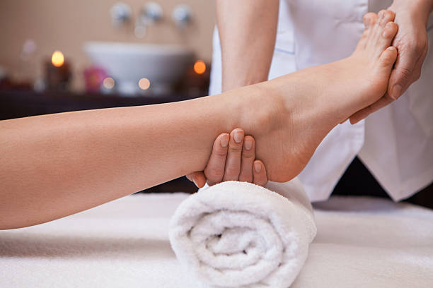Foot massage. Female hands giving massage to soft bare foot foot massage stock pictures, royalty-free photos & images