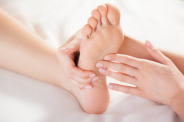 foot massage hands massaging a foot on white background foot massage stock pictures, royalty-free photos & images