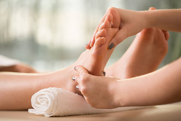 Foot massage Close-up of female hands doing foot massage foot massage stock pictures, royalty-free photos & images