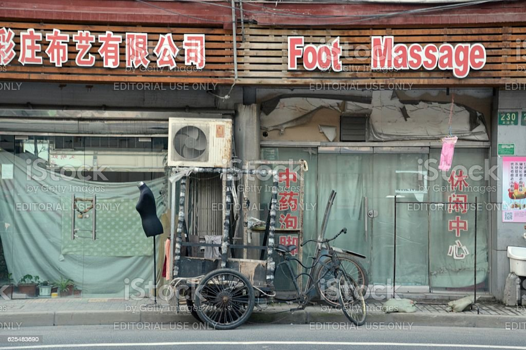 Foot Massage place and rusty tricycle in Shanghai, China stock photo