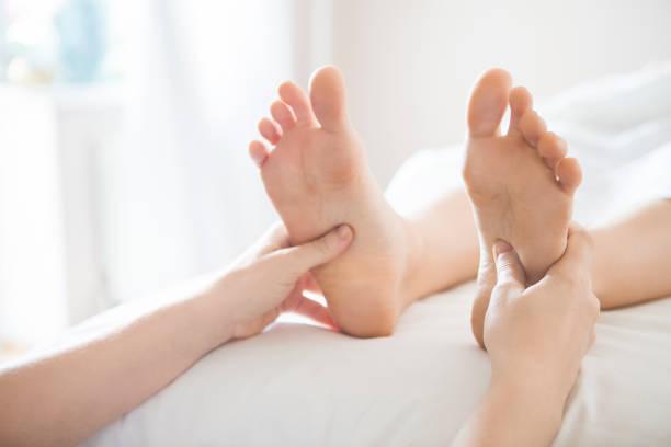Foot massage treatment in asian spa salon stock photo
