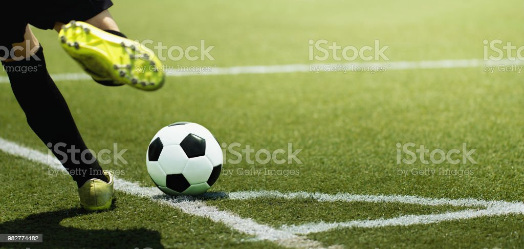 Voet van een kind football-speler en de bal op het voetbalveld - Royalty-free Activiteit Stockfoto