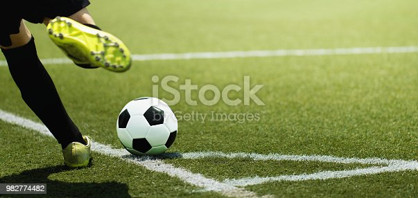 Foot of a child football player and ball on the football field, kicking a corner kick