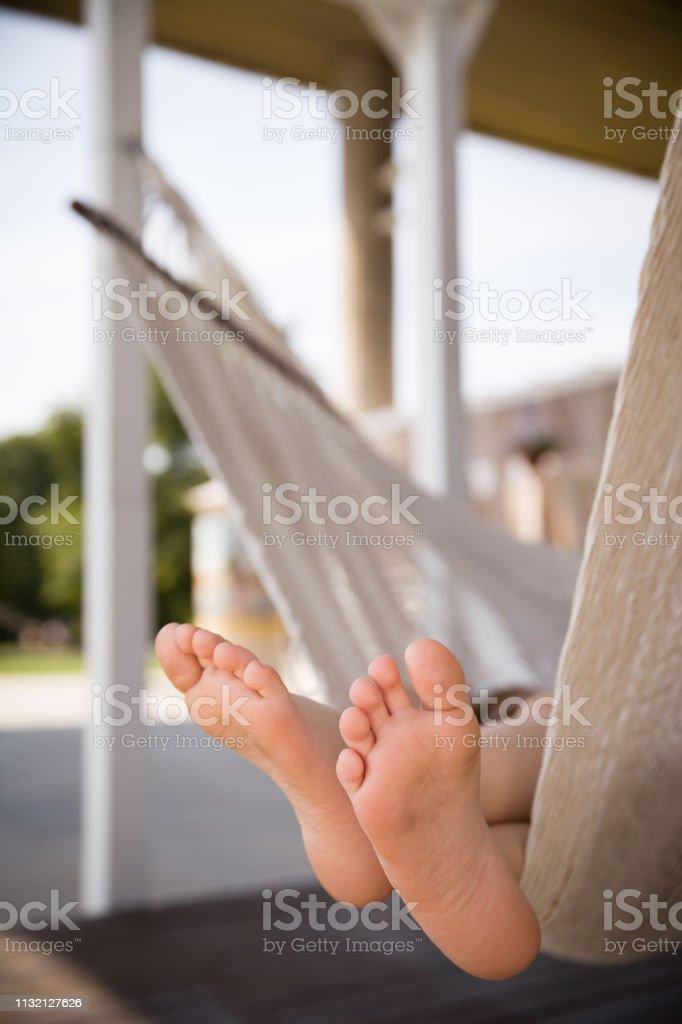 Hamakta yatan ve güneşli bir günde rahatlatıcı bir çocuğun ayak. Çıplak ayaklar. Yaşam tarzı konsepti. stok fotoğrafı