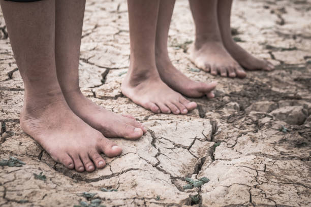 Foot of boy on cracked dry ground, Concept drought and crisis environment. stock photo
