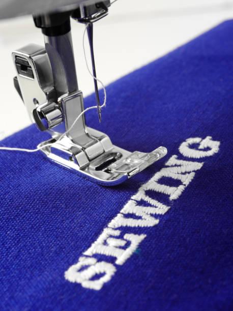 fuß der nähmaschine auf blauen stoff - maschinenstickerei stock-fotos und bilder