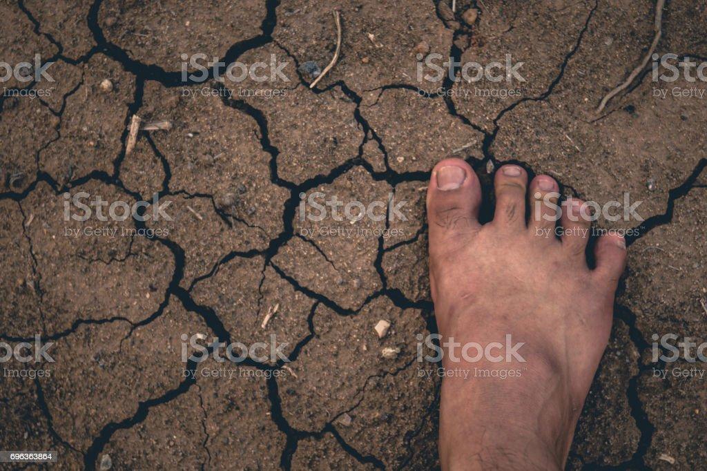 Voet op gedroogde gebarsten aarde bodem grond textuur achtergrond. foto