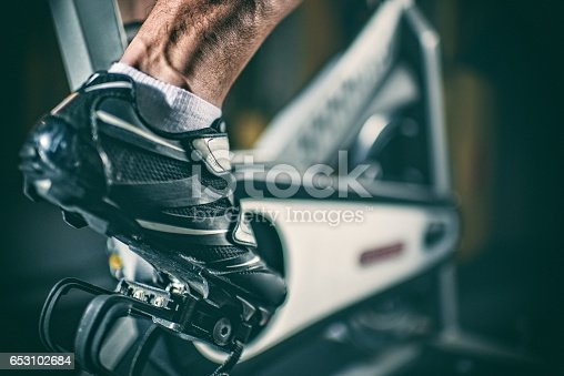 Close up view of sports shoe placed on the pedal of stationary bicycle.