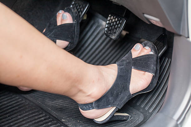 foot pressing the accelerator pedal A girl's foot with high heels pressing the accelerator pedal vehicle clutch stock pictures, royalty-free photos & images