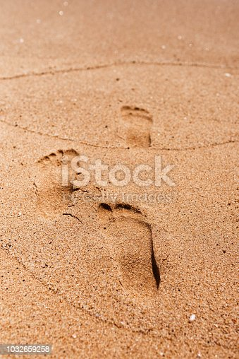 vertical textured background of foot prints on sand.