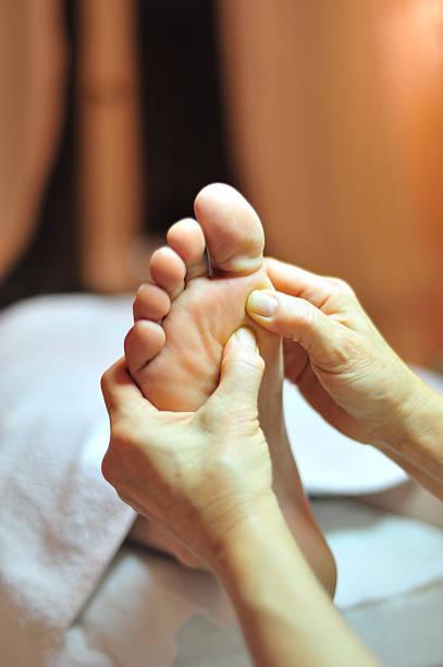 Foot reflexology massage close up stock photo