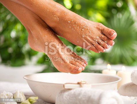 istock Foot spa on a tropical green leaves background 1131585271