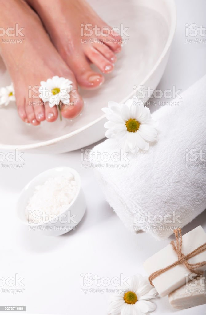 Foot spa on white background Female feet with spa bowl, towel and flowers on white background Adult Stock Photo